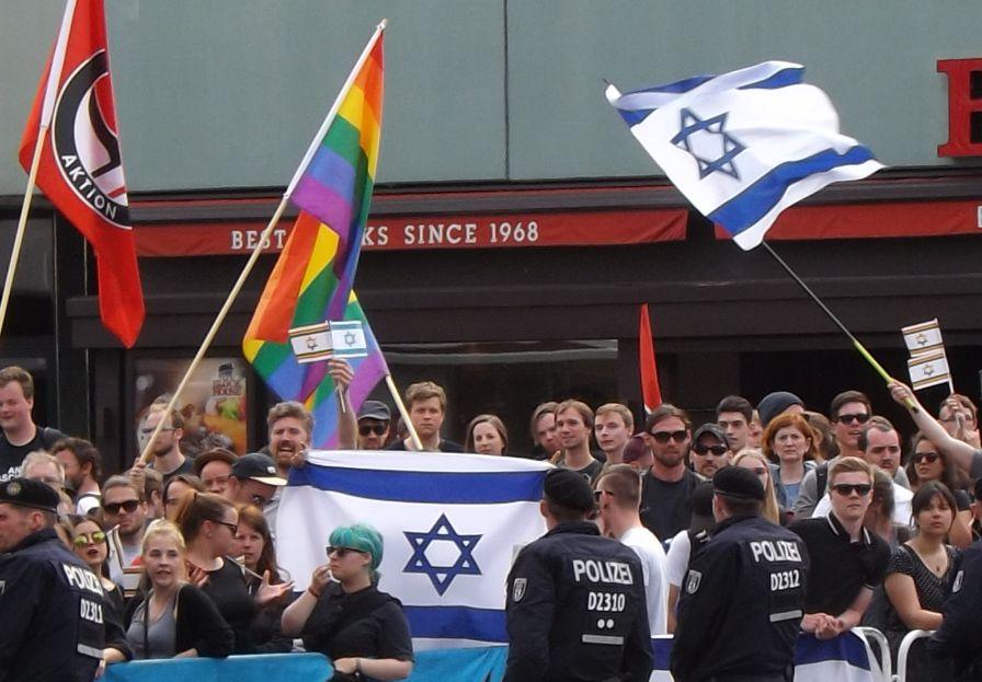 Pro-israelische Demonstranten hissen neben der israelischen Flagge die Regenbogenfahne. Berlin, Qudstag im Juli 2015.